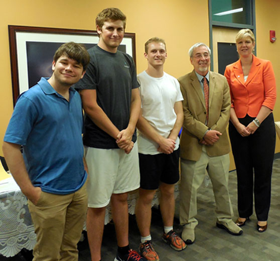 Furman celebrated the success of the drone team with a party on campus this week. From left to right are Steven Nelson, Chase Fiedler, William Lewis, John Conrad and Furman president Elizabeth Davis.