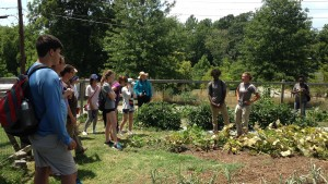 Shi Center Fellow Mary Stone gives a talk about the work her crew will do in the Mill Village Farm's Sullivan Street Garden.